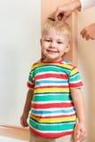 Mãos da mãe que medem o crescimento da altura da criança Fotografia de Stock Royalty Free