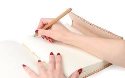 Mãos da menina com o lápis no diário pessoal Fotografia de Stock Royalty Free