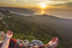Mãos da menina de assento no nascer do sol amarelo da montanha acima do mar Foto de Stock Royalty Free