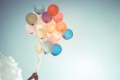 Mãos da menina que guardam balões coloridos fotografia de stock