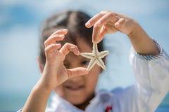 Mãos da menina que guardam uma estrela do mar fotos de stock royalty free