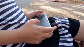 Mãos da menina que joga no smartphone vídeos de arquivo
