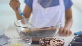Mãos da menina que misturam a massa do chocolate vídeos de arquivo