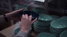 Mãos da moça que escolhem placas na seção do dishware na loja dos eletrodomésticos vídeos de arquivo