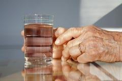 Mãos da mulher adulta e do vidro da água foto de stock royalty free