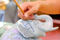 Mãos da mulher asiática tailandesa que usa a escova para tirar um teste padrão na estátua do elefante Fotografia de Stock