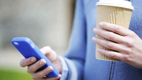 Mãos da mulher com copo de café e smartphone video estoque