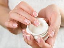 Mãos da mulher com creme Foto de Stock Royalty Free