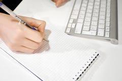 Mãos da mulher com escrita da pena no caderno no escritório Fotos de Stock