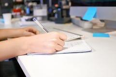 Mãos da mulher com escrita da pena no caderno no escritório Fotografia de Stock