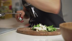 Mãos da mulher com a faca que corta brócolis Feche acima dos legumes frescos na mesa de cozinha Cozimento da dona de casa natural vídeos de arquivo