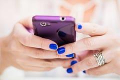 Mãos da mulher com o móbil no restaurante Imagem de Stock Royalty Free