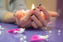 Mãos da mulher com o manicure francês que guardara uma vela Foto de Stock