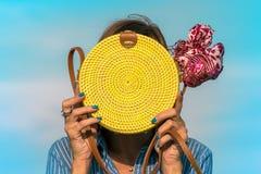 Mãos da mulher com o saco amarelo à moda elegante do rattan e o lenço da seda fora Ilha tropical de Bali, Indonésia imagem de stock