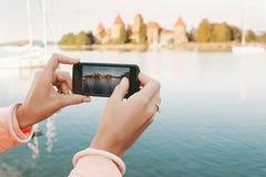 Mãos da mulher com o telefone que toma a imagem do lugar histórico Fotos de Stock Royalty Free
