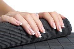 Mãos da mulher com o tratamento de mãos francês pronto para um tratamento Fotos de Stock