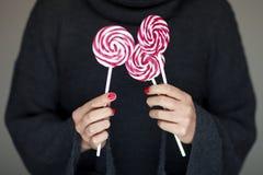 Mãos da mulher com o verniz para as unhas perfeito que guarda alguns lollypops cor-de-rosa e brancos Imagem de Stock