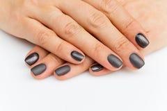 Mãos da mulher com pregos cinzentos Fotos de Stock Royalty Free