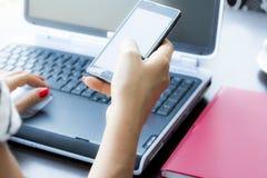 Mãos da mulher com telefone e o computador espertos no escritório Fotografia de Stock Royalty Free