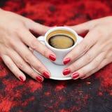 Mãos da mulher com tratamento de mãos e o copo vermelhos do café quente fresco Imagem de Stock