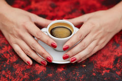 Mãos da mulher com tratamento de mãos e o copo vermelhos do café fresco imagens de stock