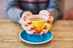 Mãos da mulher com tratamento de mãos e a xícara de café vermelhos Fotos de Stock Royalty Free