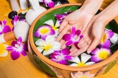 Mãos da mulher com uma bacia de água de termas do aroma na tabela de madeira Imagens de Stock