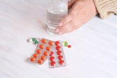 Mãos da mulher com vidro da água e dos comprimidos Imagens de Stock Royalty Free