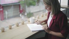 Mãos da mulher de negócio bem sucedida bonita e nova com livro em um café, lendo o livro Fêmea loura no vermelho filme