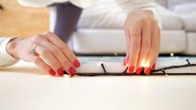 Mãos da mulher do close up enroladas na linha corda da luz a imagem filme