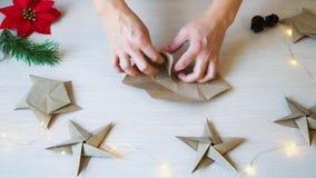 Mãos da mulher do lapso de tempo que dobram a estrela do papel do origâmi para a decoração do Natal vídeos de arquivo