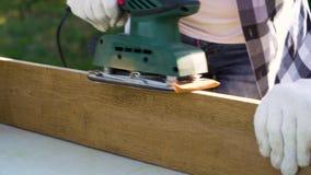 Mãos da mulher dos ofícios do close up nas luvas de trabalho que lixam a prancha de madeira com máquina de lixar filme