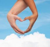 Mãos da mulher e do homem que mostram a forma do coração Imagem de Stock Royalty Free