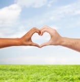 Mãos da mulher e do homem que mostram a forma do coração Foto de Stock