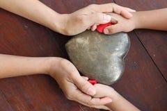 Mãos da mulher e do menino que mantêm o vermelho e o coração do metal dados forma Foto de Stock Royalty Free