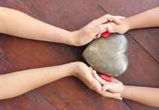 Mãos da mulher e do menino que mantêm o vermelho e o coração do metal dados forma Fotografia de Stock Royalty Free