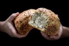 Mãos da mulher e naco de pão fotos de stock