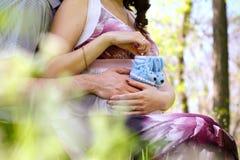 Mãos da mulher gravida e do seu marido com os sapatinhos de lã no verão p imagem de stock royalty free