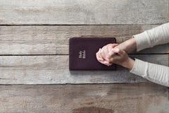 Mãos da mulher na Bíblia Fotos de Stock