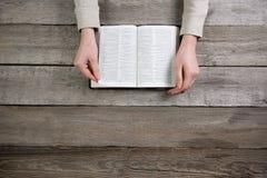 Mãos da mulher na Bíblia está lendo e está rezando Imagem de Stock
