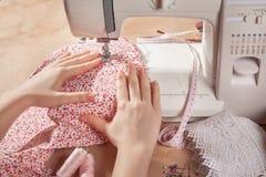 Mãos da mulher na máquina de costura Imagens de Stock