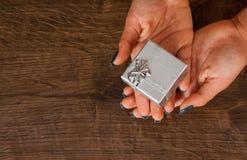 Mãos da mulher na tabela de madeira que dá a caixa de presente Imagens de Stock