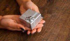 Mãos da mulher na tabela de madeira que dá a caixa de presente Foto de Stock Royalty Free