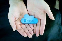 Mãos da mulher no fundo preto que guarda o ícone de Microsoft Windows OneDrive Imagens de Stock