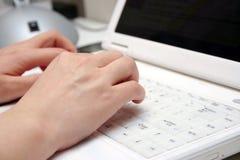 Mãos da mulher no portátil Fotografia de Stock