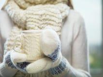 Mãos da mulher nos mitenes brancos e azuis que guardam um copo feito malha acolhedor com cacau, chá ou café quente Conceito do te fotos de stock