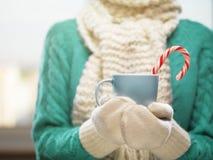 Mãos da mulher nos mitenes de lã brancos que guardam um copo acolhedor com cacau, chá ou café quente Conceito do tempo do inverno Imagens de Stock Royalty Free