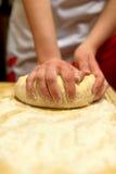 Mãos da mulher que amassam a massa de pão Fotografia de Stock