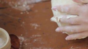 Mãos da mulher que amassam a massa na tabela cozinhando o alimento em uma cozinha vídeos de arquivo