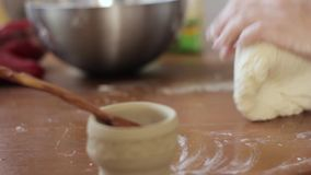 Mãos da mulher que amassam a massa na tabela cozinhando o alimento em uma cozinha filme